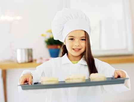 Enfant cuisinière avec pâtisserie